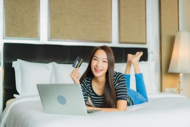 Portrait belle jeune femme asiatique utilise un téléphone mobile intelligent avec ordinateur portable et carte de crédit pour les achats en ligne