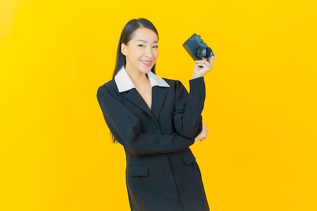 Portrait belle jeune femme asiatique utiliser un appareil photo sur un mur de couleur