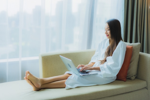Portrait belle jeune femme asiatique utiliser un ordinateur portable sur un canapé dans le salon