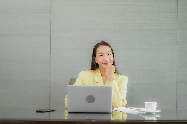 Portrait belle jeune femme asiatique utiliser un ordinateur portable avec un téléphone mobile intelligent sur la table de travail à l'intérieur de la salle