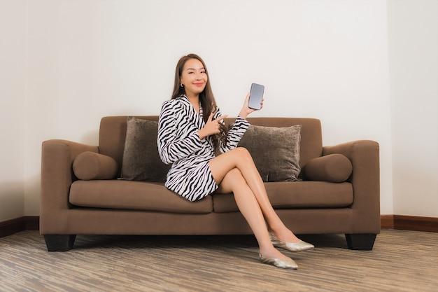Portrait belle jeune femme asiatique utiliser un téléphone mobile intelligent sur le canapé à l'intérieur du salon