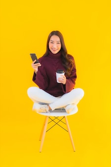 Portrait belle jeune femme asiatique utiliser un téléphone mobile intelligent sur une chaise avec fond isolé jaune