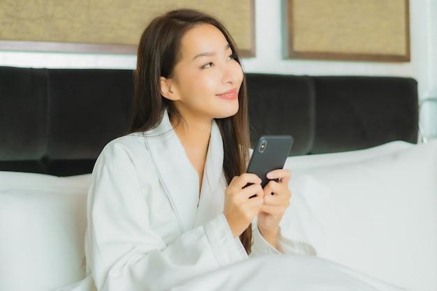 Portrait belle jeune femme asiatique utiliser un téléphone mobile intelligent sur le lit à l'intérieur de la chambre