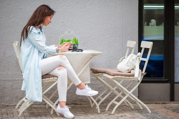 Portrait de belle jeune femme assise dans un café, boire du café en plein air. joyeux touriste au restaurant openair