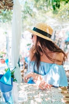 Portrait de belle jeune femme assise dans un café, boire du café en plein air.