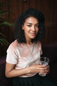 Portrait de la belle jeune femme assise dans le restaurant et regardant vers l'avant