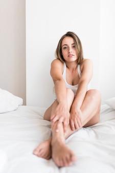 Portrait d'une belle jeune femme assise sur un lit