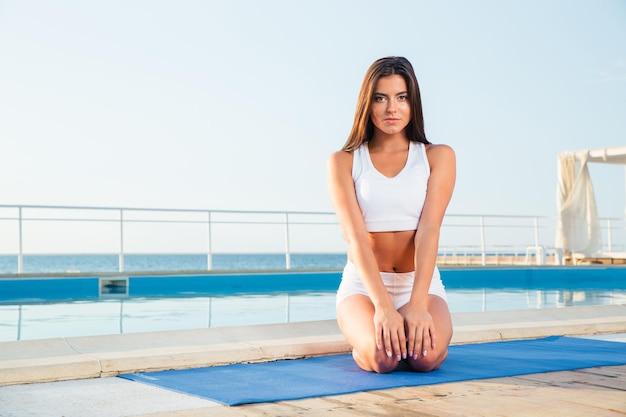 Portrait d'une belle jeune femme assise sur un tapis de yoga à l'extérieur