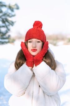 Portrait de la belle jeune femme au bonnet tricoté rouge avec bubon et mitaines en hiver à l'extérieur. cadre vertical.