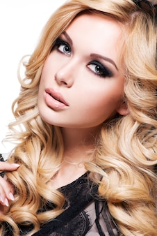 Portrait de la belle jeune femme aux cheveux blonds bouclés et maquillage sombre des yeux. mannequin sur fond blanc.