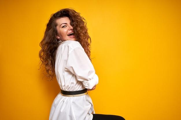 Portrait d'une belle jeune femme aux cheveux bouclés dans une chemise blanche