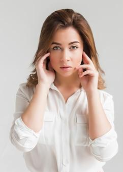 Portrait d'une belle jeune femme aux cheveux brune dans une blouse blanche et une jupe rose