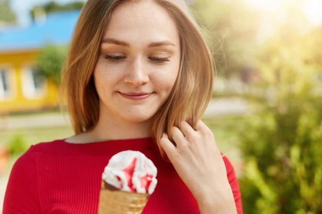 Portrait de la belle jeune femme aux cheveux clairs vêtue d'une blouse rouge