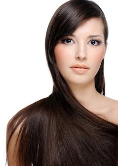 Portrait de la belle jeune femme aux cheveux longs sains luxuriants