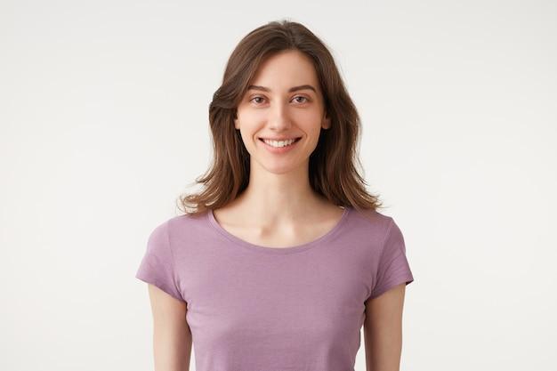 Portrait d'une belle jeune femme aux cheveux noirs avec un maquillage naturel, sourit tendrement