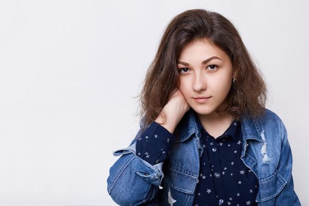 Portrait de belle jeune femme aux cheveux noirs et les yeux portant une veste en jean avec une chemise noire tenant sa main sur son cou à la recherche de confiance dans l'appareil photo.