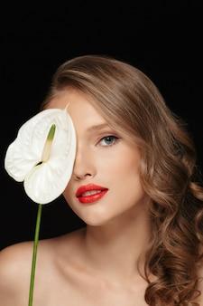 Portrait de belle jeune femme aux cheveux ondulés et lèvres rouges couvrant les yeux avec une fleur de calla blanche