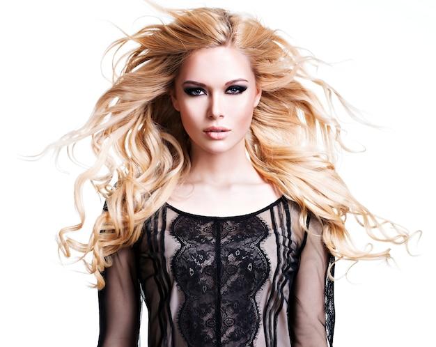 Portrait de la belle jeune femme aux longs cheveux bouclés blancs et maquillage pour les yeux foncés. mannequin posant sur un mur blanc