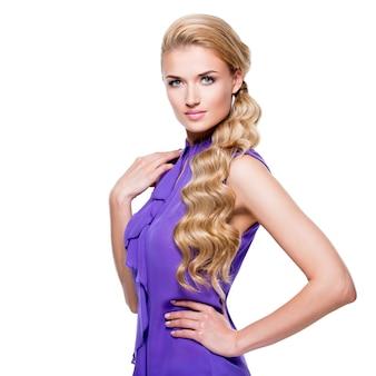 Portrait de la belle jeune femme aux longs cheveux bouclés blonds - isolé sur un mur blanc.