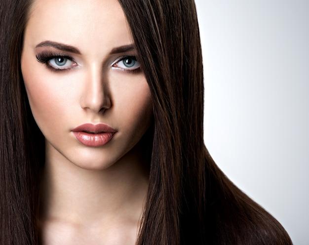 Portrait de la belle jeune femme aux longs cheveux raides au studio