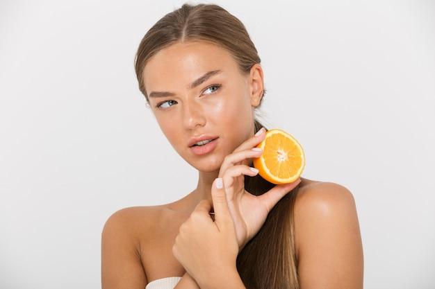 Portrait d'une belle jeune femme aux seins nus isolée, montrant des tranches d'orange