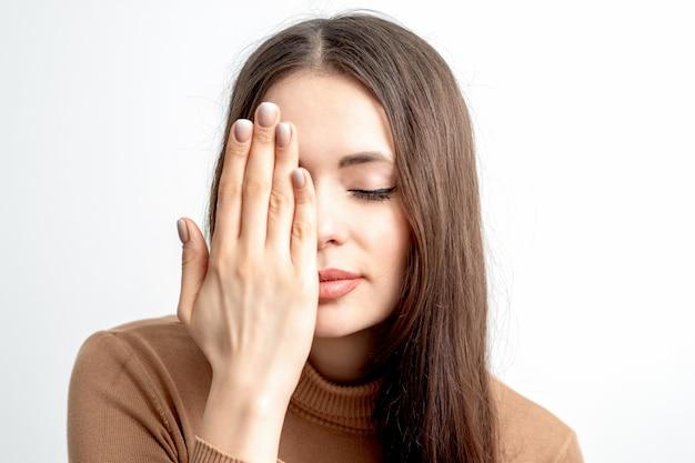 Portrait de la belle jeune femme aux yeux fermés couvrant un œil par sa main sur fond blanc