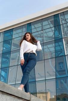 Portrait de belle jeune femme. bâtiment moderne sur fond, vue de dessous. cadre vertical.