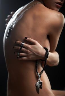 Portrait de la belle jeune femme avec des bijoux sur les mains