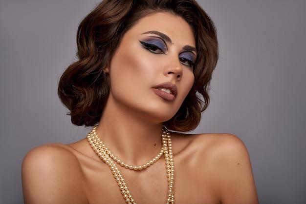 Portrait de belle jeune femme avec des bijoux en perles, collier. gros plan de visage de dame romantique. maquillage à l'ancienne et coiffure de vague de doigt