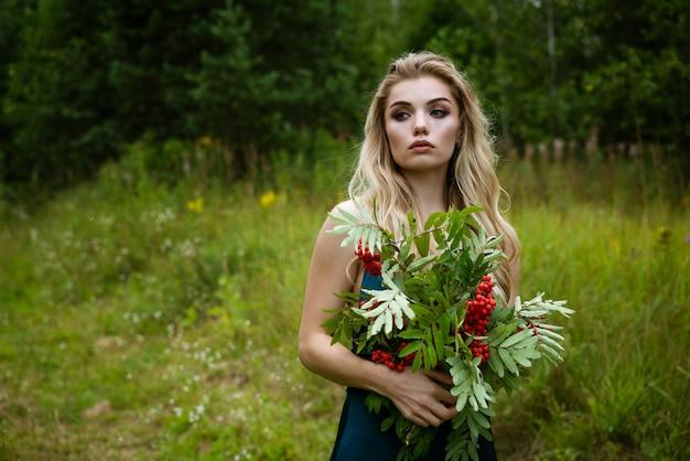 Portrait d'une belle jeune femme blonde avec un bouquet de baies de sorbier dans la nature en gros plan