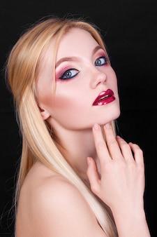 Portrait d'une belle jeune femme blonde avec du maquillage rose sur fond noir