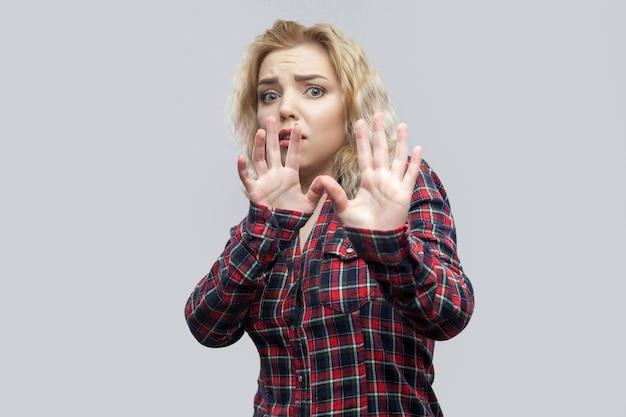 Portrait d'une belle jeune femme blonde effrayée en chemise à carreaux rouge décontractée, debout avec les mains bloquantes et la panique. tourné en studio intérieur, isolé sur fond gris.