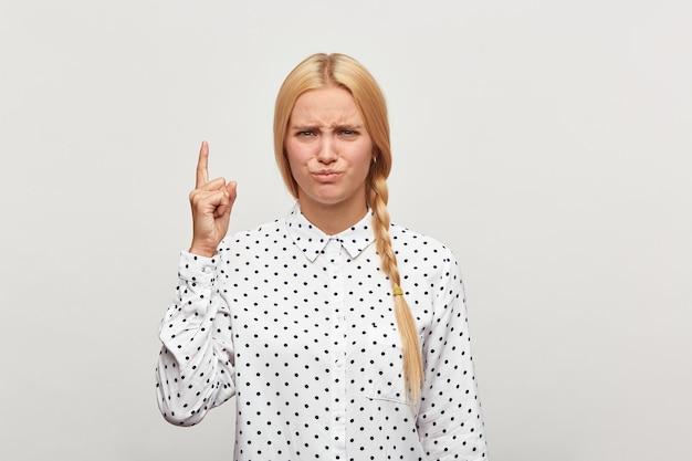 Portrait d'une belle jeune femme blonde avec un maquillage naturel et des cheveux bien coiffés réunis en tresse frustrés