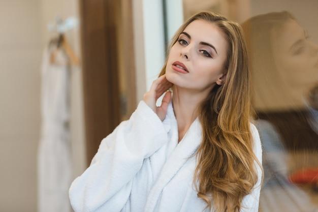 Portrait de la belle jeune femme blonde sensuelle en peignoir debout dans la salle de bain