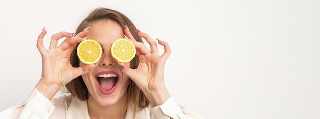 Portrait d'une belle jeune femme avec une bouche ouverte tenant deux tranches d'orange à ses yeux sur un fond blanc
