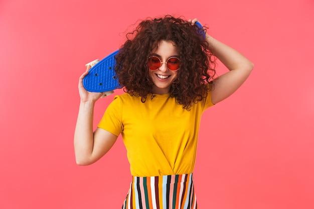 Portrait d'une belle jeune femme bouclée heureuse posant isolée sur un mur rouge avec une planche à roulettes.