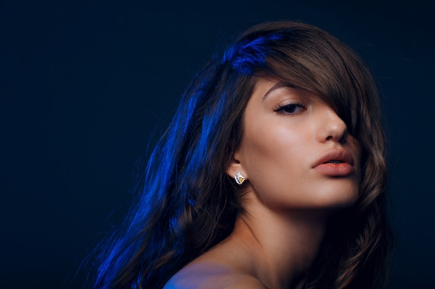Portrait de la belle jeune femme brune aux cheveux sains dans la lumière bleue