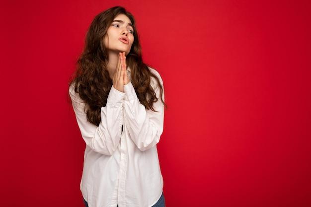 Portrait de belle jeune femme brune bouclée vêtue d'une chemise blanche isolée sur fond rouge avec