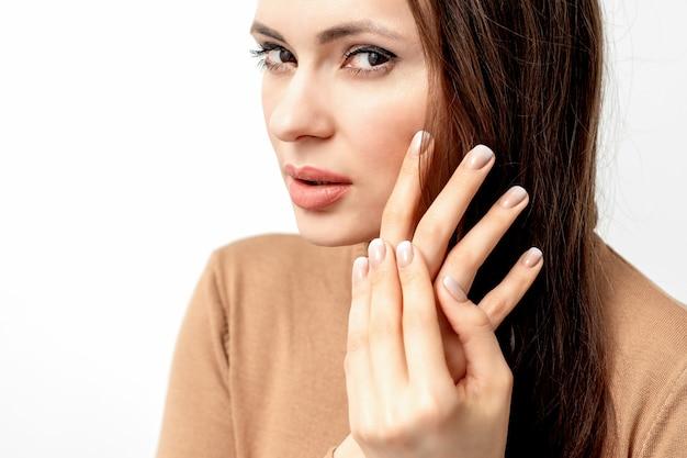 Portrait de la belle jeune femme brune caucasienne avec toucher ses cheveux par les doigts manucurés sur blanc
