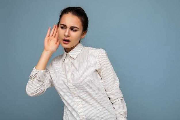 Portrait de la belle jeune femme brune avec des émotions sincères portant une chemise blanche isolée sur