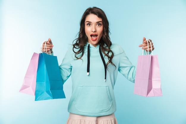 Portrait d'une belle jeune femme brune excitée debout sur bleu, portant des sacs à provisions