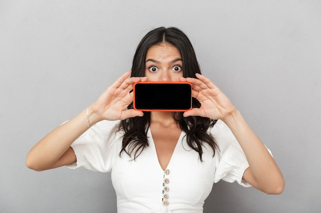Portrait d'une belle jeune femme brune excitée portant une tenue d'été isolée sur un mur gris, montrant un téléphone portable à écran blanc