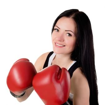 Portrait d'une belle jeune femme brune avec des gants de boxe rouges.
