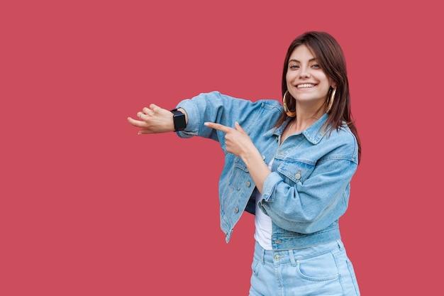 Portrait d'une belle jeune femme brune heureuse avec du maquillage dans un style décontracté en denim debout montrant et pointant sur sa montre intelligente avec un sourire à pleines dents. tourné en studio intérieur, isolé sur fond rouge.
