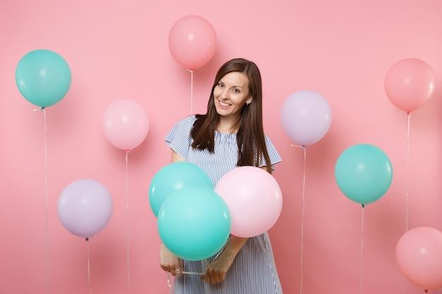 Portrait de la belle jeune femme brune heureuse souriante vêtue d'une robe bleue tenant des ballons à air colorés sur fond rose tendance lumineux. fête d'anniversaire, concept d'émotions sincères.