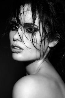 Portrait de la belle jeune femme brune avec la peau et les cheveux mouillés