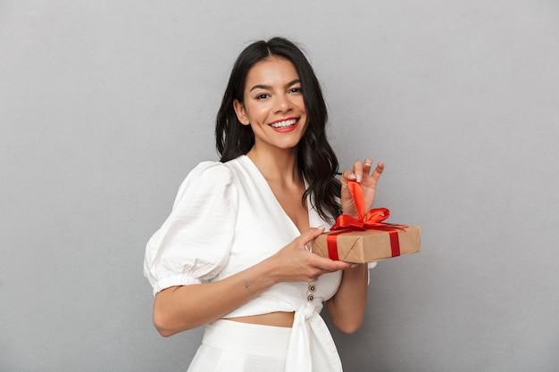 Portrait d'une belle jeune femme brune portant une tenue d'été isolée sur un mur gris, montrant une boîte présente