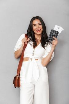 Portrait d'une belle jeune femme brune portant une tenue d'été isolée sur un mur gris, montrant un passeport avec des billets d'avion