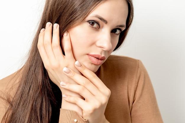Portrait de la belle jeune femme brune de race blanche avec toucher ses cheveux par un doigt manucuré sur blanc