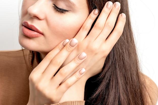 Portrait de la belle jeune femme brune de race blanche avec les yeux fermés touchant ses cheveux par les doigts manucurés